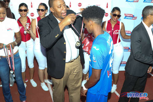 Photo: Trinidad and Tobago Football Association (TTFA) president David John-Williams (centre) presents then Naparima College attacker Jarred Dass with his 2015 National Intercol medal. (Courtesy Chevaughn Christopher/Wired868)