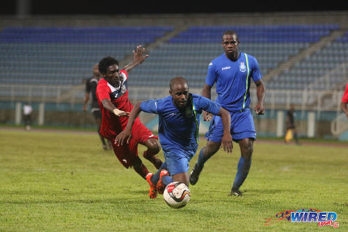 Photo: Police FC defender Dexter Alleyne (centre) tumbles under pressure from Club Sando utility player Akeem Humphrey (left) during 2015/16 Pro League action in Couva. (Courtesy Chevaughn Christopher/Wired868)