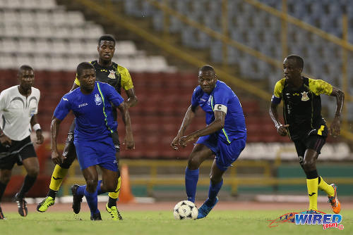 Photo: Police FC captain Todd Ryan (second from right) drives forward with the ball while his teammate Kaaron Foster (second from left), Defence Force captain Jerwyn Balthazar (right) and referee Keon Yorke (far left) look on during 2015 Pro League action last night at the Hasely Crawford Stadium. (Courtesy Allan V Crane/CA-images/Wired868)