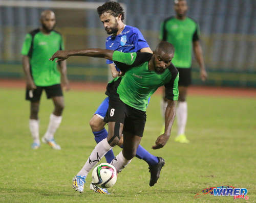 Photo: Prisons FC winger Ricardo Alleyne (foreground) keeps the ball from QPCC forward Benedict Barrett during last night's decisive CNG National Super League (NSL) Championship Division affair at the Hasely Crawford Stadium. QPCC had the playing surface narrowed to restrict Alleyne's operating room. (Courtesy Nicholas Bhajan/Wired868)