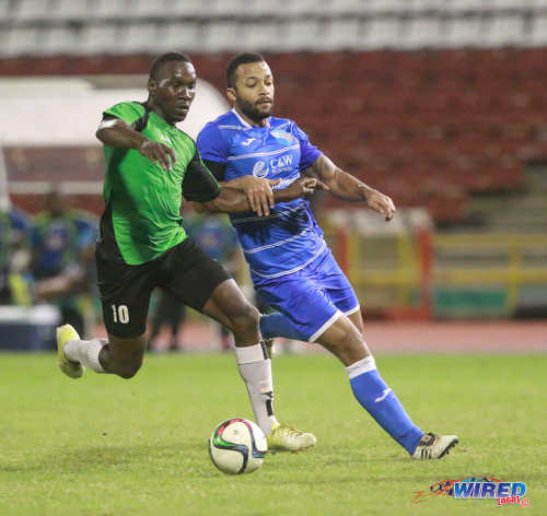 Photo: QPCC captain and midfielder Mikhail Awai (right) stays close to Prisons FC striker Curtis Carrington during last night's decisive CNG National Super League (NSL) Championship Division affair at the Hasely Crawford Stadium. (Courtesy Nicholas Bhajan/Wired868)