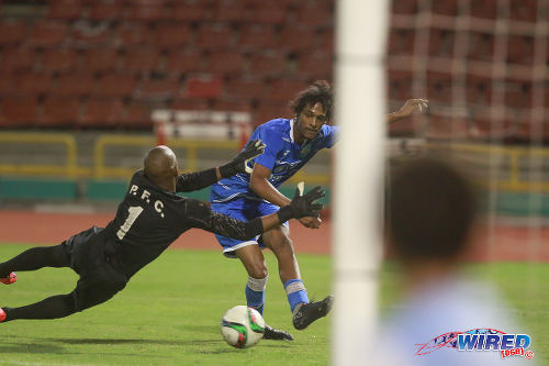 Photo: QPCC winger Mikhail Walters-Dindial (right) drives the ball below Prisons FC goalkeeper Jevon Bourne to set up the opening goal during last night's decisive CNG National Super League (NSL) Championship Division affair at the Hasely Crawford Stadium. (Courtesy Nicholas Bhajan/Wired868)