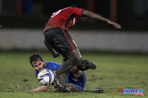 Photo: QPCC winger Jason Devenish (left) tackles UTT midfielder Stefon Pierre during 2015 CNG NSL Championship Division action last night at UTT Grounds, Arima.  (Courtesy Allan V Crane/CA-images/Wired868)