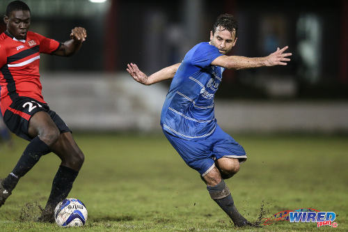 Photo: QPCC winger Jason Devenish (right) tries to elude UTT defender Ellis Roberts during 2015 CNG NSL Championship Division action at UTT Grounds, Arima.  (Courtesy Allan V Crane/CA-images/Wired868)