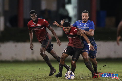 Photo: UTT midfielder Ricaldo Castellano (centre) holds off a QPCC opponent during 2015 CNG NSL Championship Division action at UTT Grounds, Arima.  (Courtesy Allan V Crane/CA-images/Wired868)