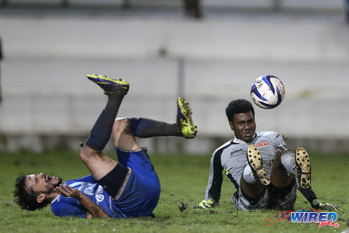 Photo: UTT goalkeeper Perry Martin (right) takes out QPCC attacker Benedict Barrett during 2015 CNG NSL Championship Division action last night at UTT Grounds, Arima.  (Courtesy Allan V Crane/CA-images/Wired868)