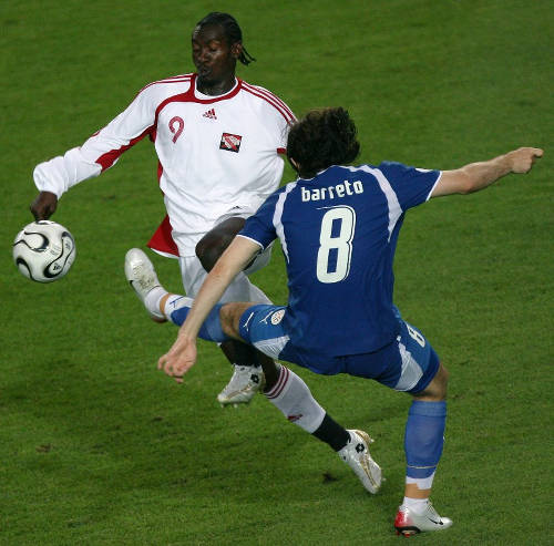 Photo: Trinidad and Tobago midfielder Aurtis Whitley (left) skips away from Paraguay player Edgar Barreto during the 2006 World Cup in Kaiserslautern. (Copyright AFP 2015/Valery Hache)