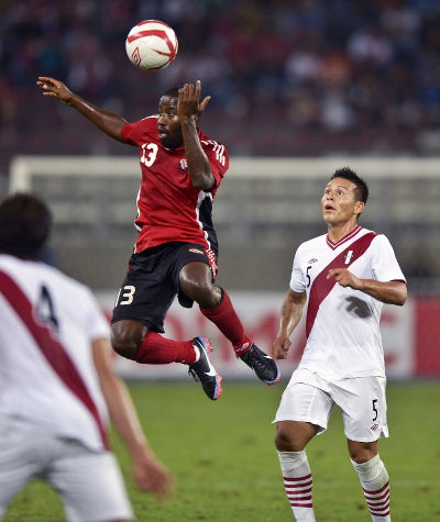 Photo: Trinidad and Tobago striker Cornell Glen (centre) beats Peru's Alfredo Rojas (right) to the ball during friendly international action in 2013. (Copyright AFP 2015/Ernesto Benavides)