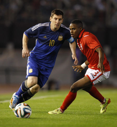 Photo: Argentina captain and icon Lionel Messi (left) in action against Trinidad and Tobago's Joevin Jones during friendly international action in June 2014 in Buenos Aires. (Courtesy TTFA Media)