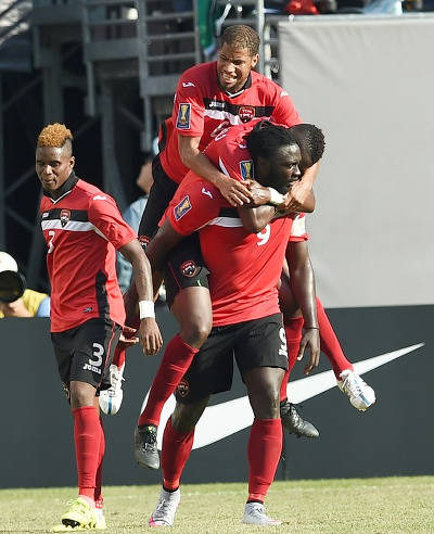 Photo: Trinidad and Tobago captain Kenwyne Jones (right) gives Radanfah Abu Bakr and another teammate a ride after scoring against Panama in the 2015 CONCACAF Gold Cup quarterfinal round. Looking on is Joevin Jones (left). (Copyright AFP 2015/Jewel Samad)
