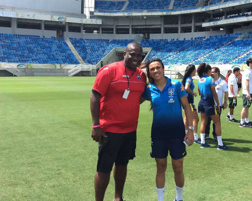 Photo: Trinidad and Tobago stand-in women's head coach Anthony Creece (left) poses with Brazil star Marta before the game. (Courtesy TTFA Media)