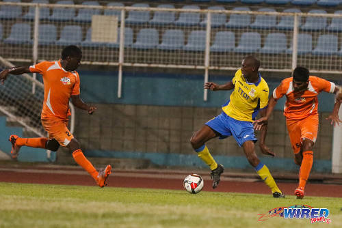Photo: Defence Force attacker Hashim Arcia (centre) takes on Club Sando players Amritt Gildharry (right) and Devon Modeste during 2015/16 Pro League action in Couva yesterday. (Courtesy Chevaughn Christopher/Wired868)