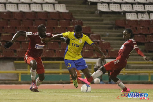 Photo: Defence Force winger Kishun Seecharan (centre) tries to drive past Central FC players Jamal Jack (left) and Darren Mitchell during 2015/16 Pro League action yesterday at the Hasely Crawford Stadium. (Courtesy Chevaughn Christopher/Wired868)