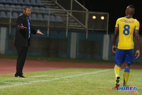Photo: Defence Force coach Marvin Gordon (left) reacts to a late penalty kick awarded by referee Dennis Changiah during Pro League action against Club Sando at the Ato Boldon Stadium in Couva. Looking on is Defence Force player Curtis Gonzales. (Courtesy Chevaughn Christopher/Wired868)