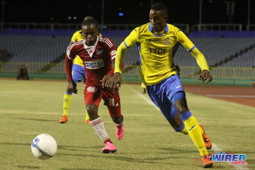 Photo Defence Force winger Ross Russell Jr (right) hustles past Central FC midfielder Darren Mitchell during 2015/16 Pro League action yesterday at the Hasely Crawford Stadium. (Courtesy Chevaughn Christopher/Wired868)
