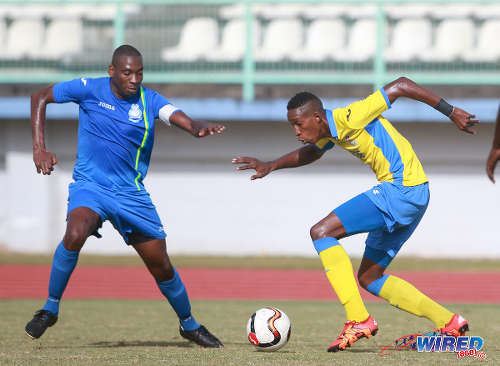 Photo: Defence Force winger Ross Russell Jr (right) tries to sneak past Police FC midfield sentry Todd Ryan during 2015/16 Pro League action yesterday in Malabar. (Courtesy Nicholas Bhajan/Wired868)