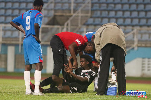 Photo: Central FC attacker Jason Marcano (seated) gets some treatment for what appeared to be a broken finger during 2015/16 Pro League action yesterday against St Ann's Rangers. (Courtesy Chevaughn Christopher/Wired868)