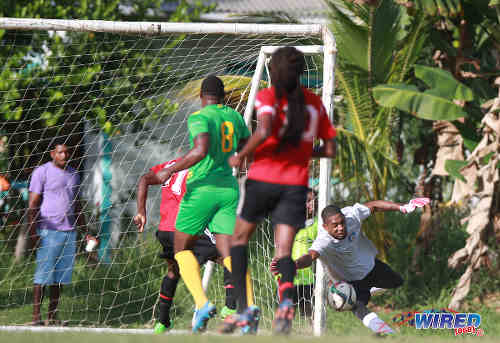 Photo: Guaya United captain Erskine Johnson (right) tries in vain to stop a cross from reaching Matura ReUnited goal scorer Dorian Robinson during 2015/16 CNG NSL Premiership Division action in Matura. (Courtesy Nicholas Bhajan/WIred868)