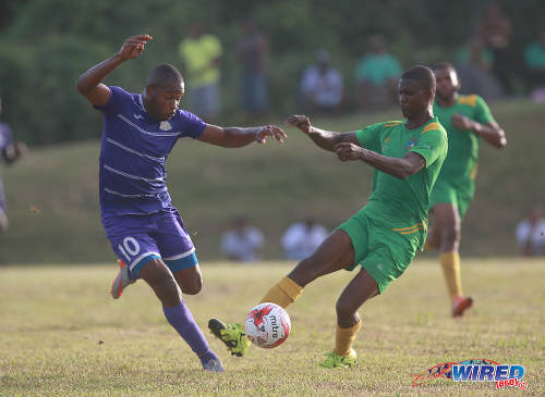Photo: Defence Force attacker Josimar Belgrave (left) tries to find a way past Guaya United defender Sherlon Campbell during 2015/16 CNG National Super League action yesterday in Guayaguare. (Courtesy Nicholas Bhajan/Wired868)