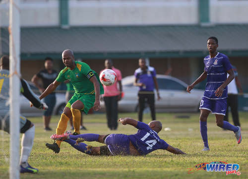 Photo: Defence Force stopper Dwight Scott (centre) dives in to tackle Guaya United captain Ryan Stewart while Army left back Tevin Balfour looks on during 2015/16 CNG National Super League action in Guayaguare. (Courtesy Nicholas Bhajan/Wired868)