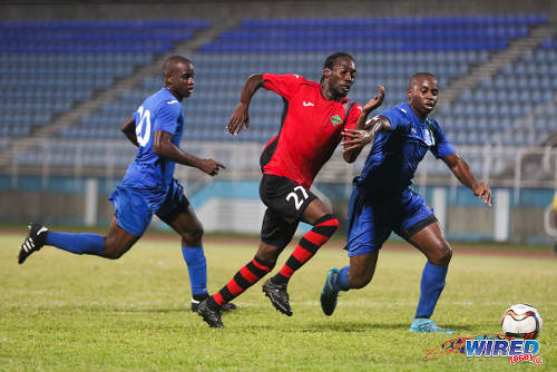 Photo: San Juan Jabloteh winger Nathan Lewis (centre) terrorises the Police FC defence during 2015/16 Pro League action in Couva. (Courtesy Chevaughn Christopher/Wired868)