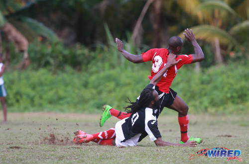 Photo: Petrotrin Palo Seco defender Wayne Huyghue (left) makes a vain attempt to stop Matura ReUnited attacker Dorian Robinson during CNG National Super League Premiership Division action at the Matura Recreation Ground yesterday. (Courtesy Nicholas Bhajan/Wired868)