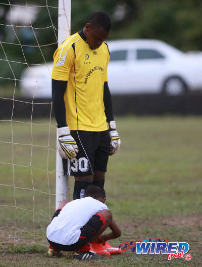 Photo: Matura ReUnited goalkeeper Glenroy Samuel (standing) gets some help from a young football during CNG National Super League Premiership Division action against Petrotrin Palo Seco at the Matura Recreation Ground. (Courtesy Nicholas Bhajan/Wired868)