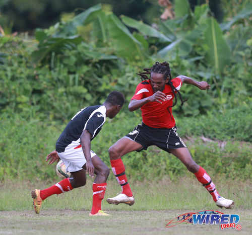 "Photo: Matura ReUnited captain and winger Sherwin ""Bulbie"" Charles (right) takes on Petrotrin Palo Seco full back Isaiah Garcia during CNG National Super League Premiership Division action at the Matura Recreation Ground yesterday. (Courtesy Nicholas Bhajan/Wired868)"