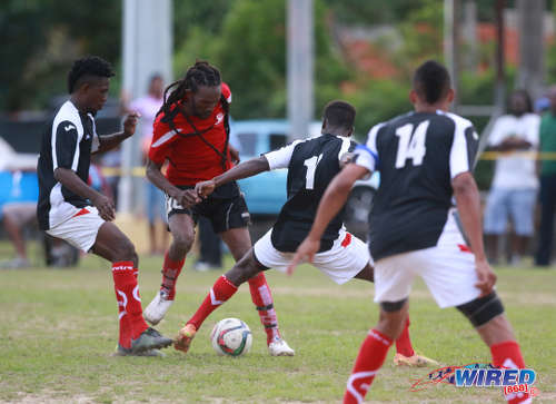 "Photo: Matura ReUnited captain and star midfielder Shervin ""Bulbie"" Charles (centre) is crowded out by Petrotrin Palo Seco players (from right) Cebastian Bailey, Isaiah Garcia and Xavier Seales during 2015/16 CNG National Super League Premiership Division action at the Matura Recreation Ground. (Courtesy Nicholas Bhajan/Wired868)"