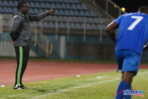 Photo: Police FC coach Richard Hood (left) gives a thumbs up during 2015/16 Pro League action yesterday against Defence Force. (Courtesy Chevaughn Christopher/Wired868)