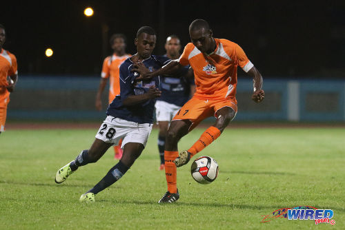 Photo: Club Sando midfielder Jared London (right) holds off Morvant Caledonia United attacker Pernell Schultz during 2015/16 Pro League action at the Ato Boldon Stadium, Couva. (Courtesy Chevaughn Christopher/Wired868)