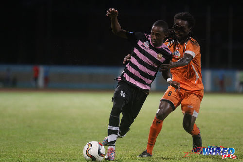 Photo: North East Stars attacker Jomoul Francois (left) tries to escape from Club Sando midfielder Ryan Frederick during Pro League action yesterday in Couva. (Courtesy Chevaughn Christopher/Wired868)