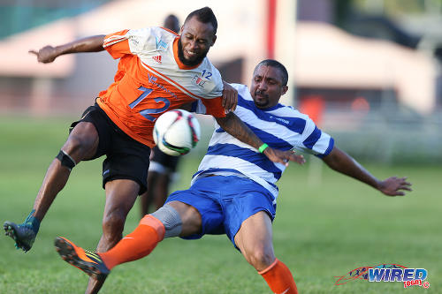 Photo: Former Trinidad and Tobago attacker Gary Glasgow (left) tries to avoid a tackle from Wired868 XI left back Gregory Seale during the 4th Annual Wired868 Football Festival at UWI SPEC Grounds, St Augustine. (Courtesy Allan V Crane/CA-images/Wired868)