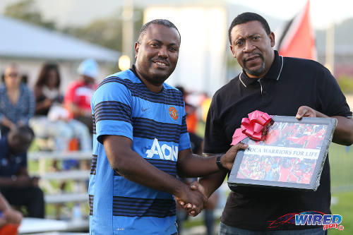 "Photo: Trinidad and Tobago Football Association (TTFA) president David John-Williams (right) presents a Wired868 token of appreciation to ""Soca Warriors"" supporter Peter Cumberbatch during the 4th Annual Wired868 Football Festival at UWI SPEC Grounds, St Augustine on Saturday 2 January 2016. (Courtesy Allan V Crane/CA-images/Wired868)"