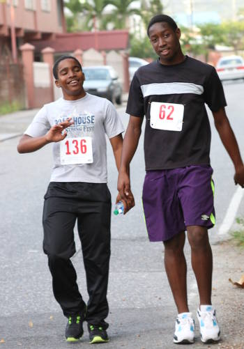 Photo: Two Arima North Secondary students take it easy during a 5k against school violence and bullying on Friday February 12. (Courtesy Arima North Secondary)