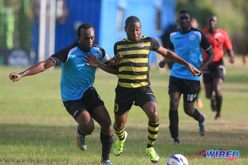 Photo: Defence Force attacker Josimar Belgrave (right) holds off WASA defender and captain Akil Harley during CNG National Super League Premiership Division action yesterday in St Joseph. (Courtesy Nicholas Bhajan/Wired868)