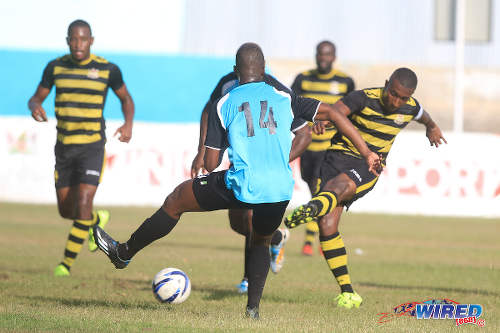 Photo: Defence Force captain and midfielder Christopher Durity (right) shoots past WASA defender Christopher Mitchell during CNG National Super League Premiership Division action in St Joseph. (Courtesy Nicholas Bhajan/Wired868)