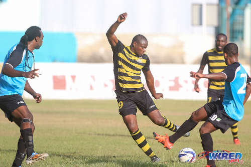 Photo: Defence Force forward Michael Edwards (centre) prepares to shoot the ball past WASA FC defenders Dillon Peterson (right) and Akil Harley during CNG National Super League Premiership Division action yesterday in St Joseph. (Courtesy Nicholas Bhajan/Wired868)