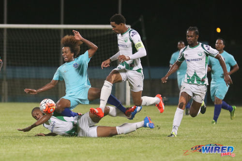 Photo: Atlantico FC winger Bryan Gonzales (second from left) is chopped down by a tackle from W Connection midfielder Briel Thomas (left) while Gerard Williams (far right) and Alvin Jones look on during 2016 Caribbean Club Championship action last night in Couva. (Courtesy Chevaughn Christopher/Wired868)