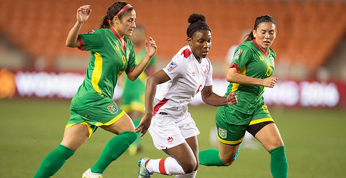 Photo: Canada's 16 year old rising star Deanne Rose (centre) terrorises the Guyana defence during 2016 Olympic qualifying action on Thursday. (Courtesy CONCACAF)