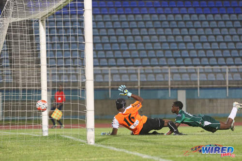 Photo: W Connection attacker Dimitrie Apai (right) beats Club Sportif Moulien goalkeeper Fabien Beral during 2016 Caribbean Club Championship action in Couva on 26 February 2016. (Courtesy Chevaughn Christopher/Wired868)
