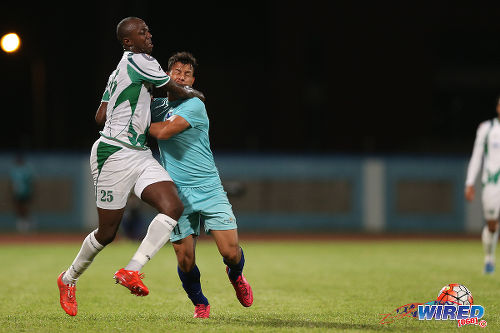 Photo: W Connection defender Daneil Cyrus (left) tangles with Atlantico FC flanker Adrian De Jesus in Caribbean Club Championship action last night in Couva. (Courtesy Allan V Crane/CA-images/Wired868)