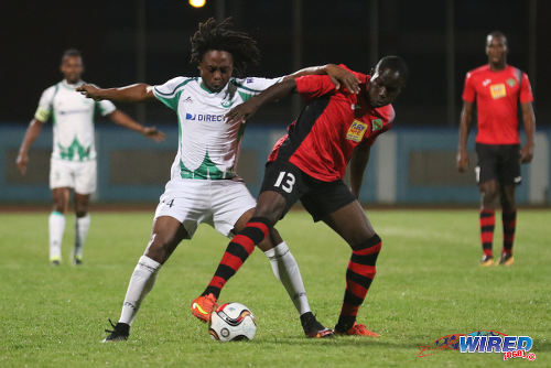 Photo: Battle of the maestros. San Juan Jabloteh midfielder Fabian Reid (right) tries to hold off W Connection playmaker Andre Toussaint during 2015/16 Pro League action at the Ato Boldon Stadium. (Courtesy Chevaughn Christopher/Wired868)