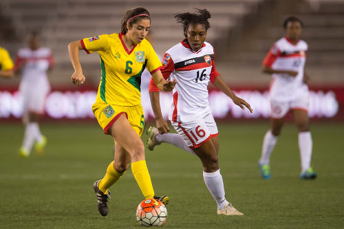 Photo: Trinidad and Tobago forward Jo Marie Lewis (right) tries to close down Guyana defender Leah Ramalho during CONCACAF 2016 Olympic qualifying action last night in Houston. (Copyright CONCACAF)