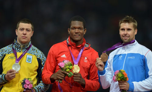 Photo: Trinidad and Tobago's Keshorn Walcott (centre) shows off his gold medal at the London 2010 Olympics. Anthony N Sabga has joined the country's elite gold medal club for his deft finish in the artistic tendering event. (Copyright AFP 2016/Johannes Eisele)