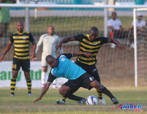 Photo: WASA FC midfielder Kevon Henry (foreground) tries to keep possession during CNG National Super League Premiership Division action yesterday in St Joseph. (Courtesy Nicholas Bhajan/Wired868)
