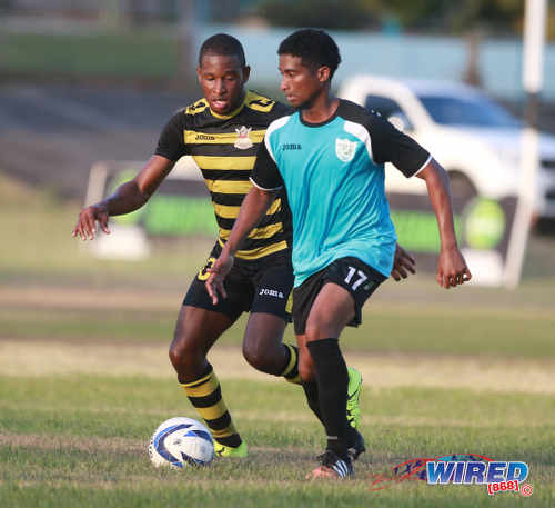 Photo: WASA attacker Shane Calderon (right) tries to keep the ball away from Defence Force star Josimar Belgrave during CNG National Super League Premiership Division action yesterday in St Joseph. (Courtesy Nicholas Bhajan/Wired868)