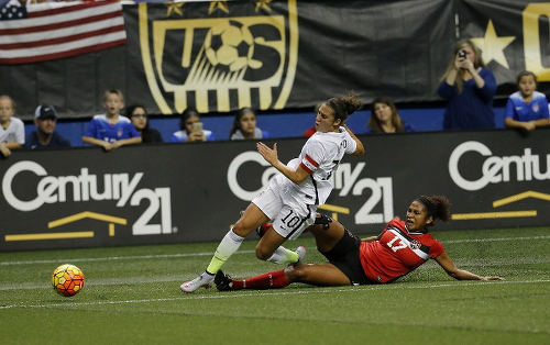 Photo: Trinidad and Tobago midfield anchor Victoria Swift (right) chops down United States captain Carli Lloyd during international friendly action in December 2015. (Copyright AFP 2016/Chris Covatta)