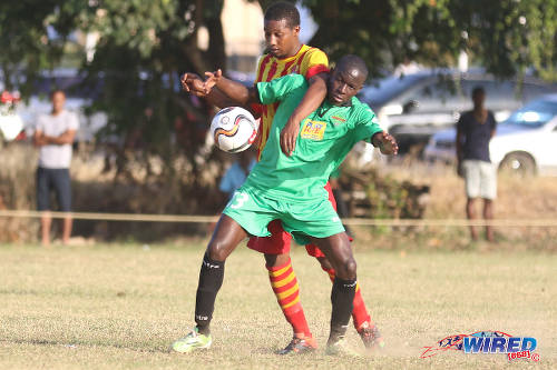 Photo: San Juan Jabloteh playmaker Fabian Reid (right) tries to hold off a Point Fortin Civic player during TT Pro League action at the Barataria Recreation Ground, Barataria on 5 March 2016. (Courtesy Chevaughn Christopher/Wired868)