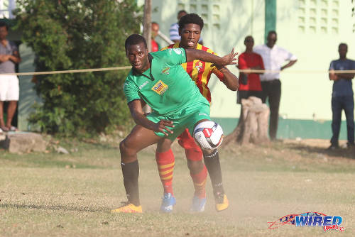 Photo: San Juan Jabloteh forward Jamal Gay (foreground) tries to hold off a Point Fortin Civic opponent during TT Pro League action at the Barataria Recreation Ground, Barataria on 5 March 2016. (Courtesy Chevaughn Christopher/Wired868)